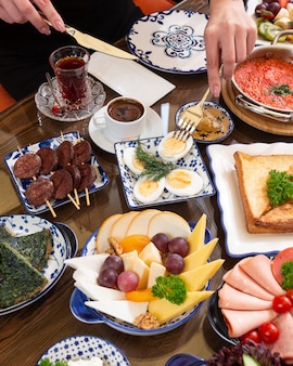 Side view of various plates of food fo breakfast as fried eggs toasts tea with sweetness