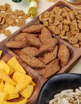 Vista laterale di vari snack di birra salata cracker di pane coni di mais su un piatto di legno e semi di girasoli e olive in salamoia su bianco