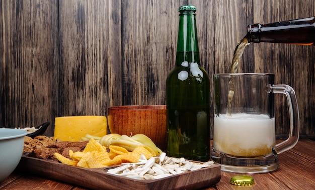 Vista laterale di vari spuntini salati della birra su un vassoio di legno e birra di versamento in una tazza su legno rustico