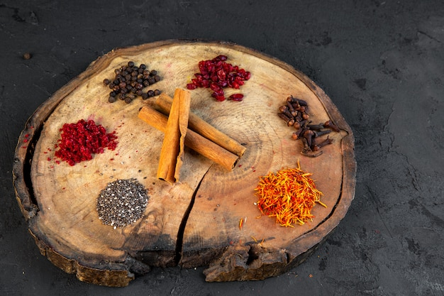 Side view of various spices saffron chili powder black pepper and cinnamon sticks on round wooden board