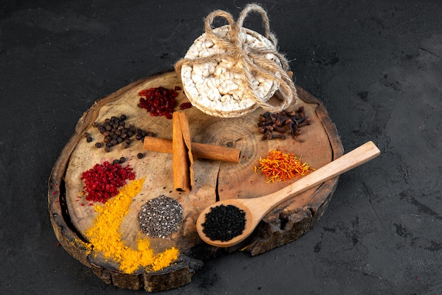 Side view of various spices a wooden spoon with black seeds and rice breads tied with a rope on wooden board on black