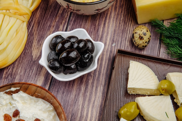 Side view of various type of cheese with black pickled olives and quail eggs on rustic wood
