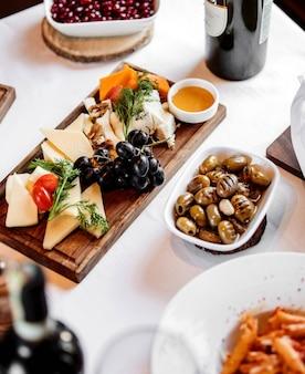 Vista laterale di vari tipi di formaggio con miele e uva sul piatto di legno con olive in salamoia