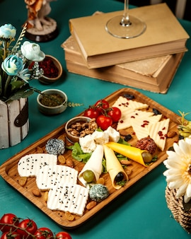Side view of various types of cheese with nuts grapes and cherry tonatoes on wooden platter