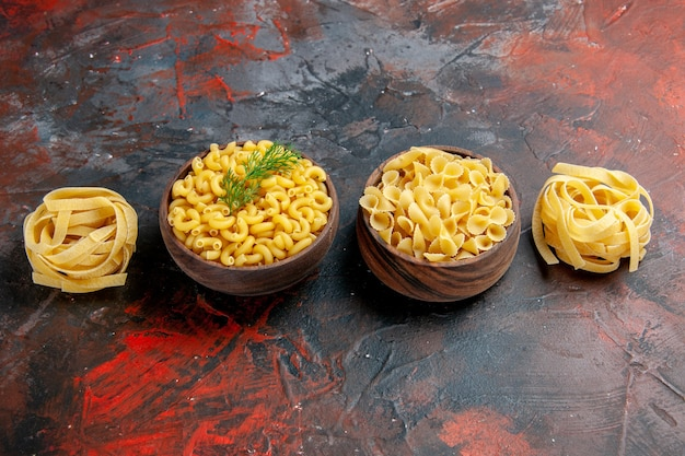 Side view of various types of uncooked pastas on mixed color background
