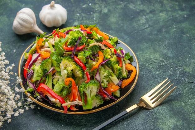 Vista laterale dell'insalata vegana in un piatto e forchetta all'aglio fiore bianco su sfondo scuro