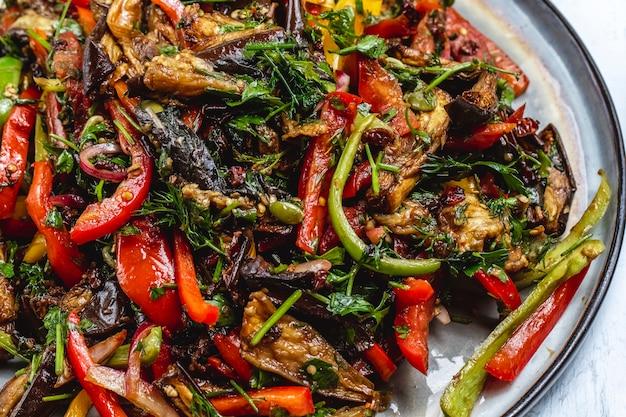 Вид сбоку овощное рагу тушеное из баклажанов лук зелень томатный зеленый и красный перец на тарелке