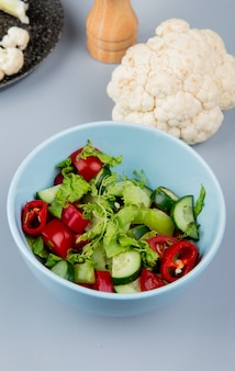 Side view of vegetable salad in bowl with cauliflower on blue background