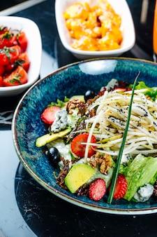 Вид сбоку овощной салат с фруктами клубникой и виноградом в тарелке