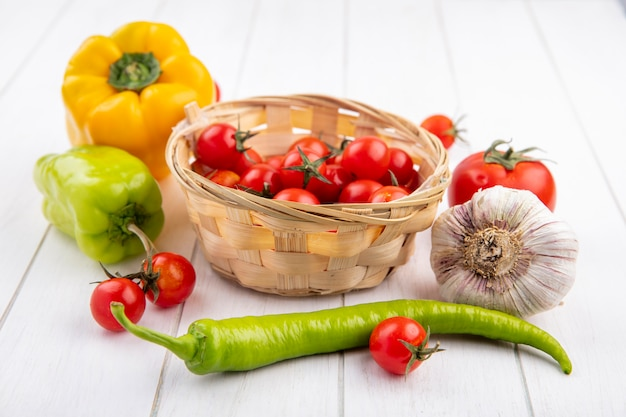 Vista laterale di verdure come cesto di pomodoro con bulbo di aglio pepe e pomodori intorno su legno