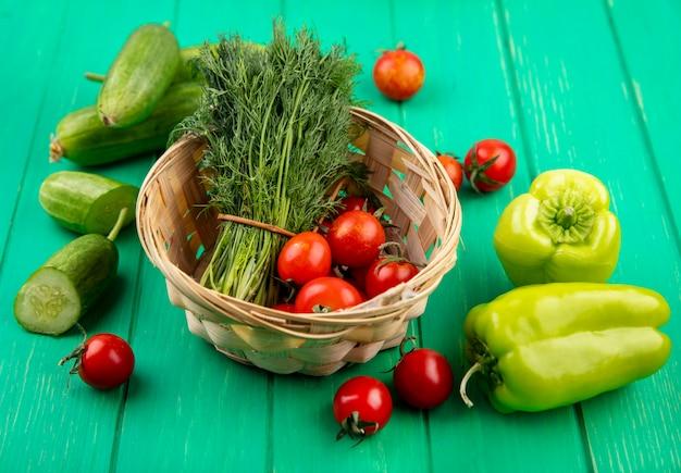 Vista laterale di verdure come mazzo di aneto e pomodori nel carrello con cetrioli tagliati peperoni e pomodori sul verde