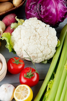 Side view of vegetables as cauliflower celery tomato cabbage garlic with cut lemon on wooden background