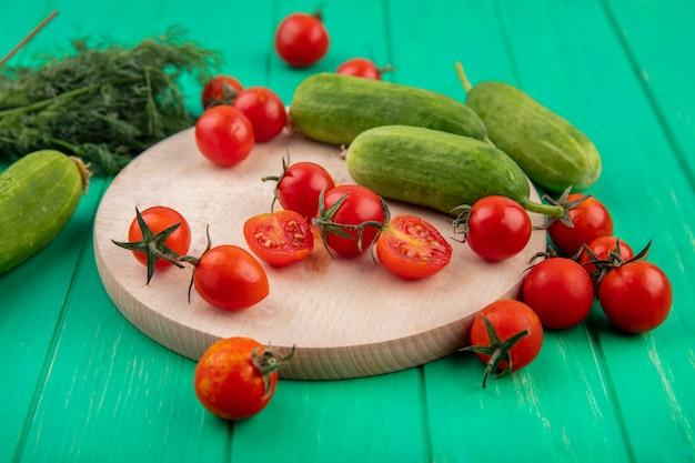 Vista laterale di verdure come cetriolo e pomodoro sul tagliere e mazzo di aneto sul verde