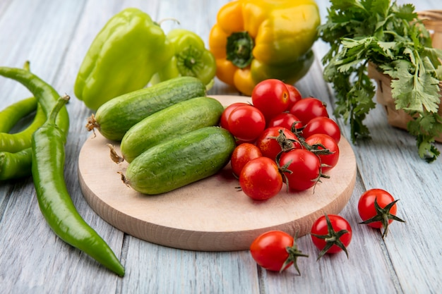 Vista laterale di verdure come pomodoro cetriolo sul tagliere con pepe e coriandolo su legno con spazio di copia