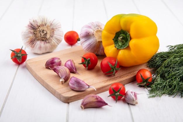 Vista laterale di verdure come aglio, pomodoro, pepe sul tagliere con aneto su legno