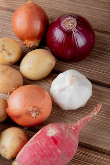 Side view of vegetables as onion potato garlic and radish on wooden background