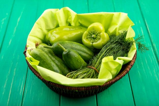 Vista laterale delle verdure come merce nel cestino dell'aneto del cetriolo del pepe sul verde