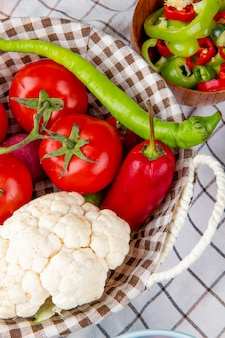 Side view of vegetables as pepper tomato cauliflower in basket with vegetable salad on plaid cloth background