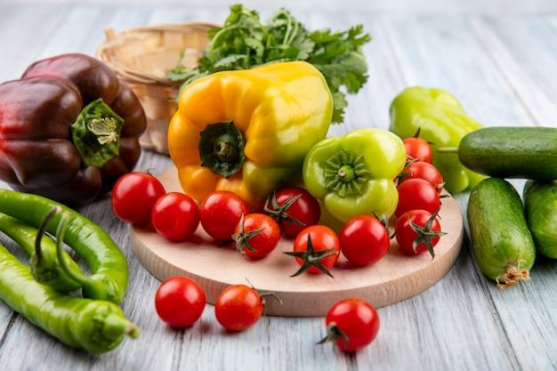 Vista laterale di verdure come pepe e pomodoro sul tagliere con cetriolo e aneto su legno