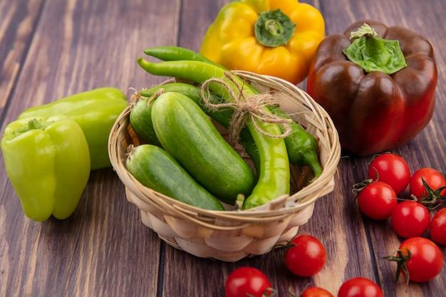 Vista laterale della merce nel cestino delle verdure come pepe e cetriolo con i pomodori intorno su legno