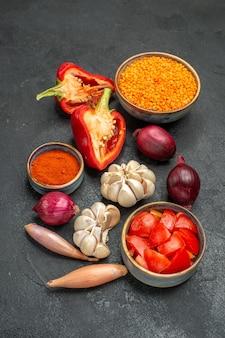 Vista laterale verdure cipolla aglio lenticchie peperoni pomodori spezie sulla tavola nera