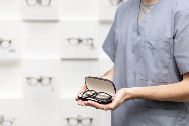 Side view view of man holding on pair of glasses in case