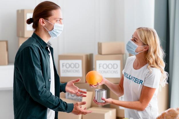 Вид сбоку на добровольца, раздающего еду в качестве пожертвования