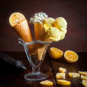 Вафельные рожки с апельсином, мороженым и гипсофилой в чашке для мороженого, вид сбоку