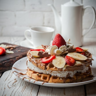 Side view waffle ice cream cake with strawberry and cup and teapot in round white plate