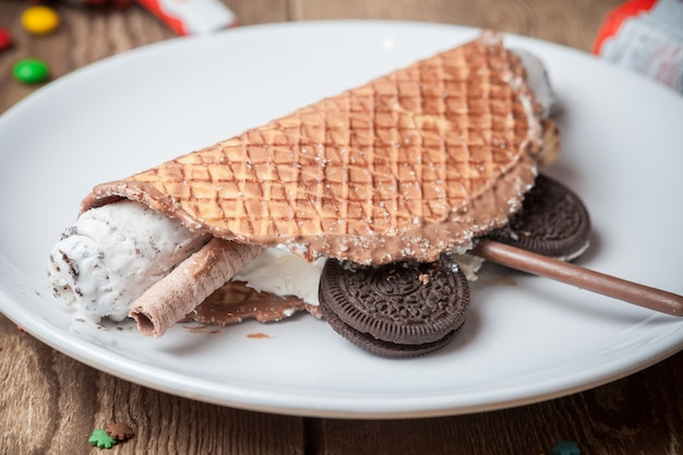 Side view waffle ice cream with chocolate chip cookies in round white plate