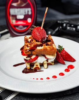 Side view of waffle with ice cream strawberries and bananas covered with chocolate sauce on white plate