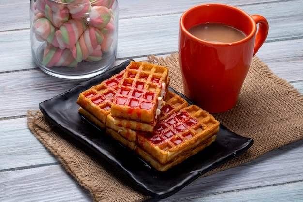 Side view of waffles with strawberry syrup on a black platter and a cup of cocoa