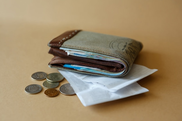 Side view of wallet with money coins and cashiers check from store