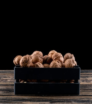 Side view walnuts in black box on wooden horizontal