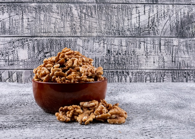 Side view walnuts in bowl on stone horizontal