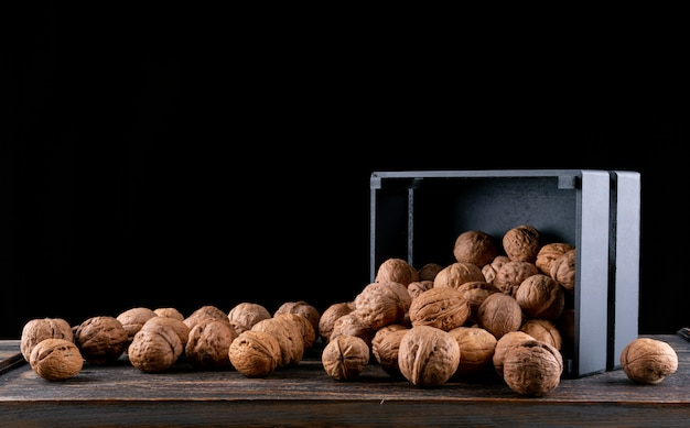 Side view walnuts from black box on wooden horizontal
