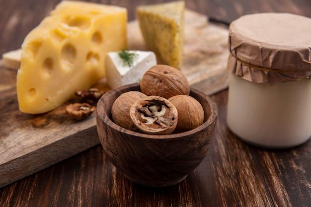 Vista laterale noci con varietà di formaggi su un supporto con yogurt in un barattolo su uno sfondo di legno