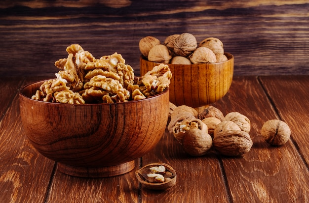 Side view of walnuts in a wooden bowl on dark rustic background