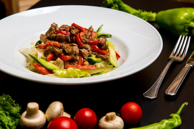 Вид сбоку теплый салат с мясом и овощами с грибами и помидорами