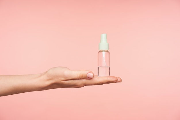 Side view of well-groomed female's hand keeping palm up while holding transparent spray bottle with liquid on it, isolated against pink background