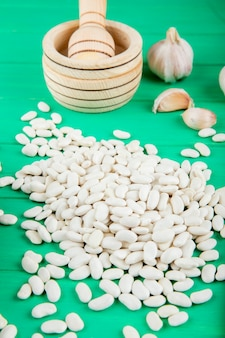 La vista laterale dei fagioli bianchi ha sparso sulla tavola di legno verde