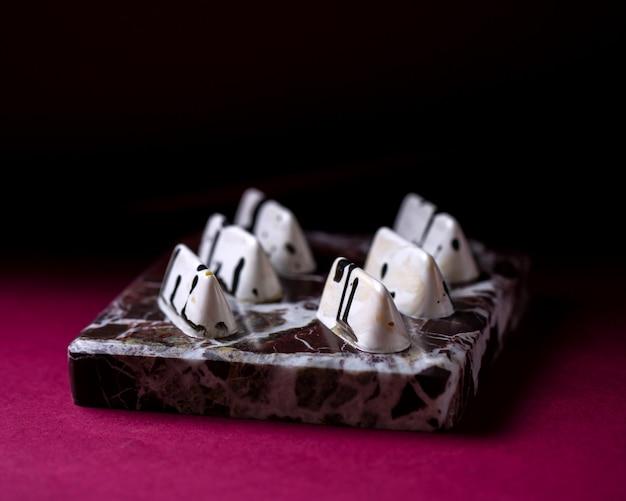Bianco di vista laterale in caramella di cioccolato nera sul supporto