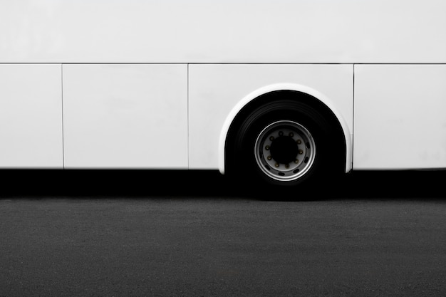 Side view of a white bus wheel on an asphalt road.
