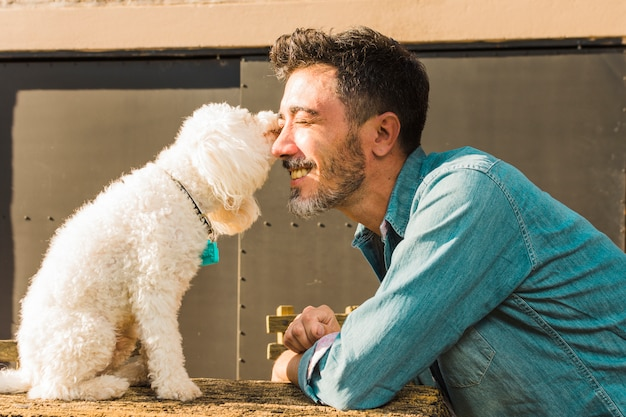 Side view of white dog kissing his smiling male pet owner