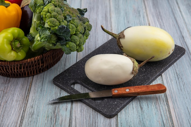 Side view of white eggplants with knife on cutting board and peppers  broccoli in basket on wooden background