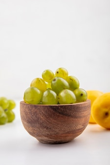 Side view of white grape berries in bowl with nectacots on white background