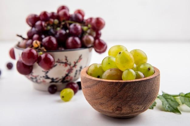 Vista laterale di acini d'uva bianca e uva rossa in ciotole con acini d'uva e foglie su sfondo bianco