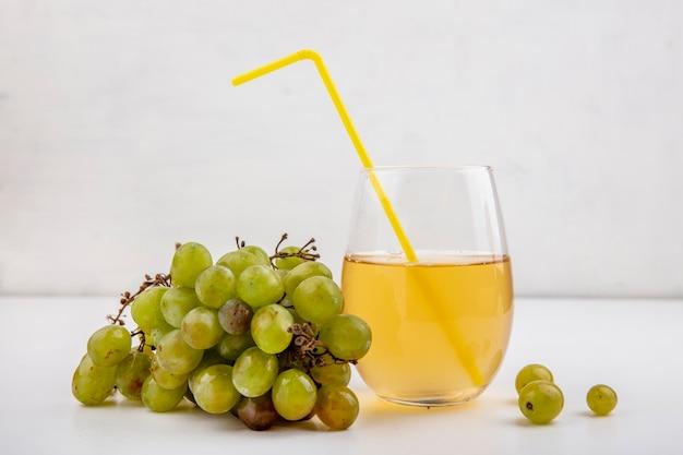 Vista laterale di uva bianca e succo d'uva in vetro su sfondo bianco