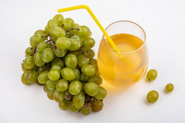 Vista laterale di uva bianca e succo d'uva con tubo per bere in vetro su sfondo bianco