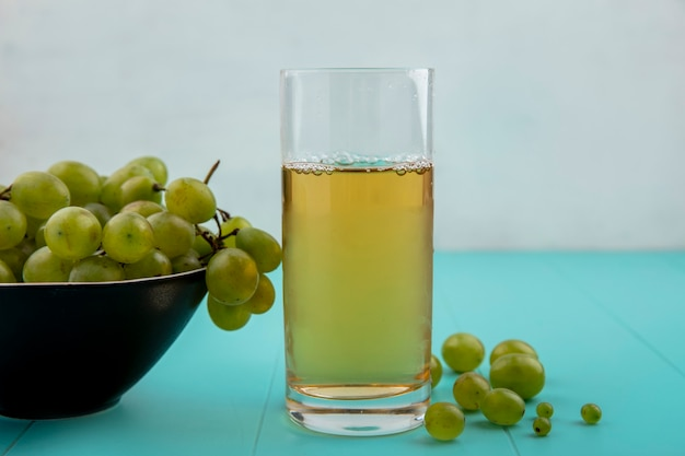 Side view of white grape juice in glass and bowl of grape with grape berries on blue surface and white background